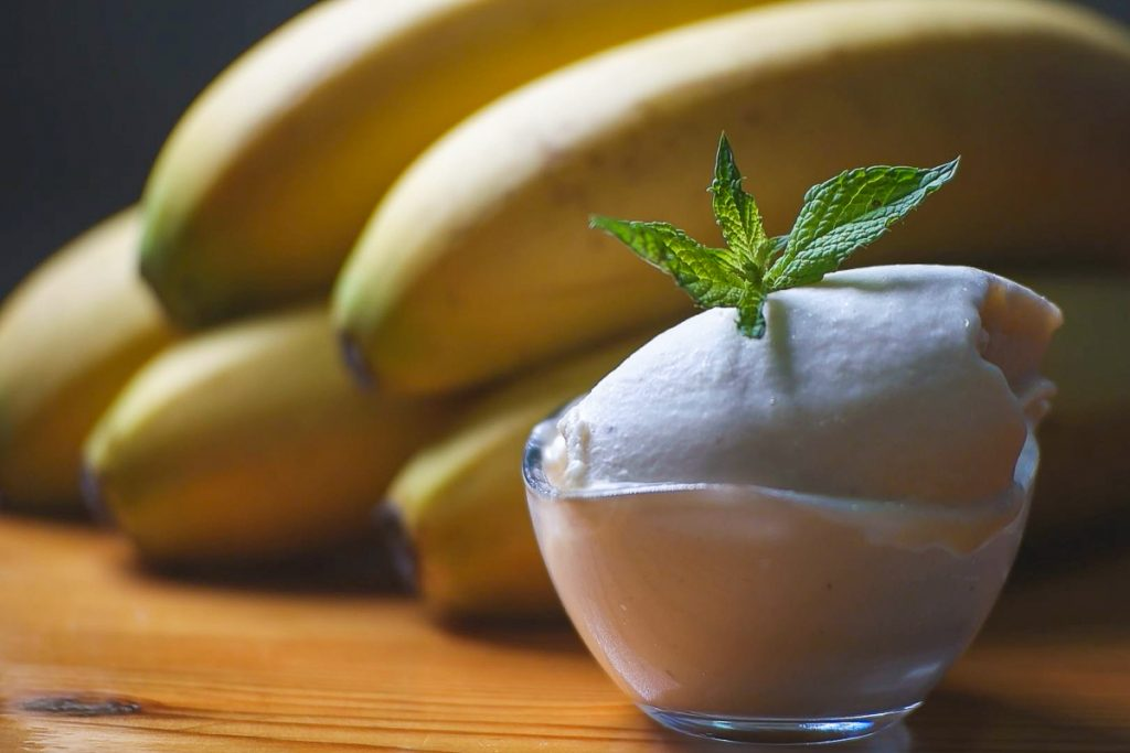 Una bolita de helado de plátano y detrás unos plátanos
